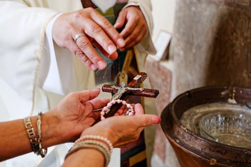 Um rosário e um crucifixo da bênção do padre com água santamente imagens de stock