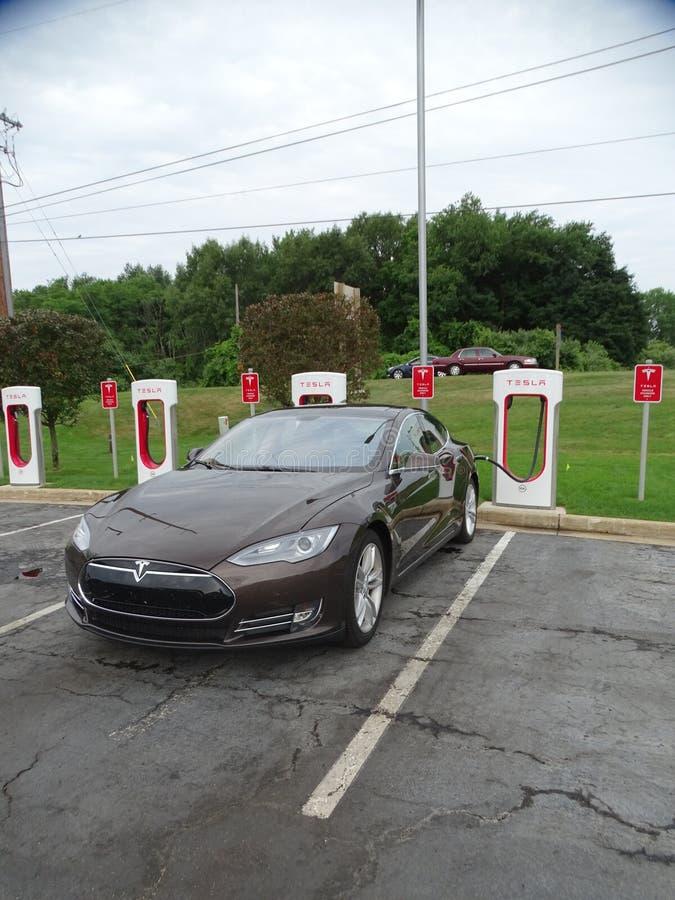Um ` s da bateria de carro de Tesla que recarrega a estação com um carro de Tesla estacionou nos vagabundos de carregamento fotografia de stock