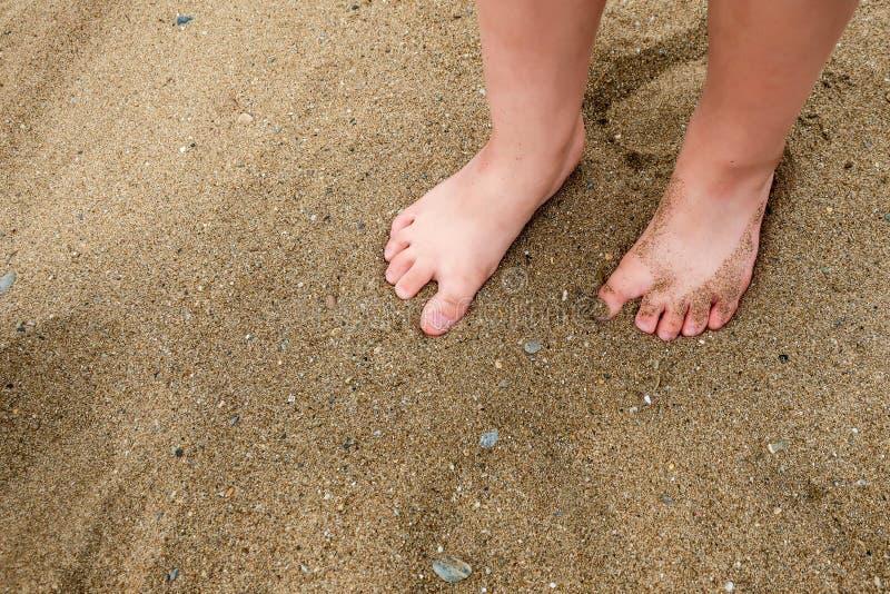 Um ` s da menina/pés ` s da criança na areia em uma praia imagem de stock