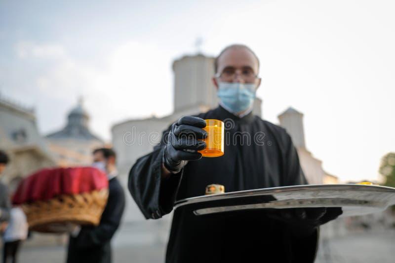 Um sacerdote cristão ortodoxo com máscara cirúrgica devido à pandemia de 19 anos partilha a Santa Luz durante a Páscoa ortodoxa fotografia de stock royalty free