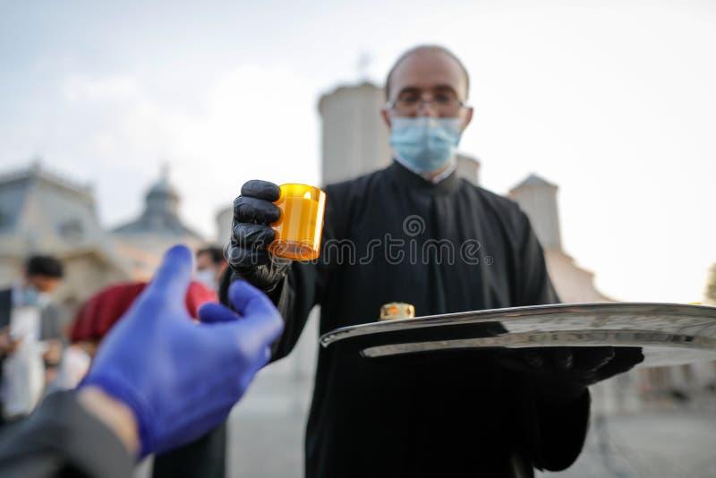 Um sacerdote cristão ortodoxo com máscara cirúrgica devido à pandemia de 19 anos partilha a Santa Luz durante a Páscoa ortodoxa fotos de stock royalty free