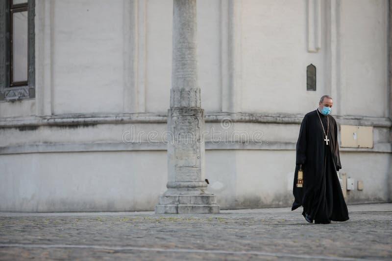 Um sacerdote cristão ortodoxo com máscara cirúrgica devido à pandemia de 19 anos transporta a Santa Luz durante a Páscoa ortodoxa imagem de stock