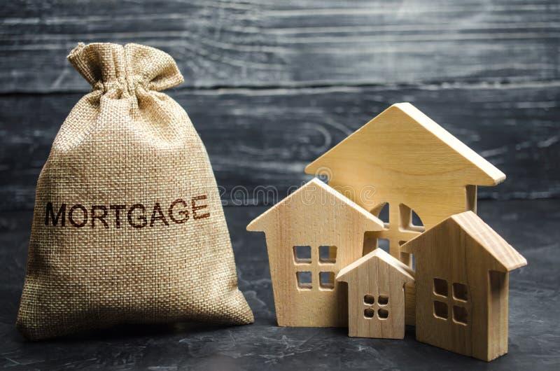 Um saco com dinheiro e a hipoteca da palavra e casas de madeira A acumulação de dinheiro para pagar taxas de juro em hipotecas A  fotos de stock