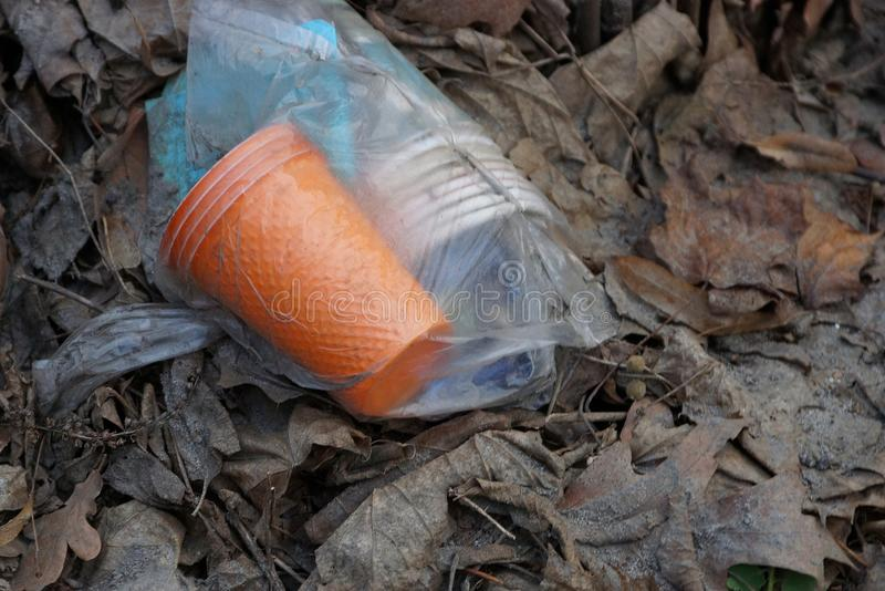 Um saco do lixo está encontrando-se nas folhas secas fora fotografia de stock