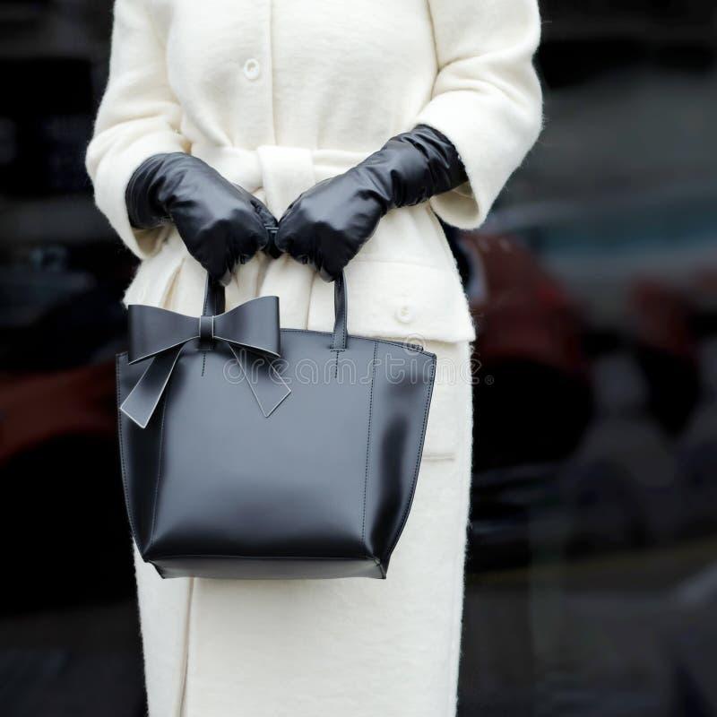 Um saco nas mãos de uma mulher A menina em um revestimento na moda Close-up fotos de stock royalty free
