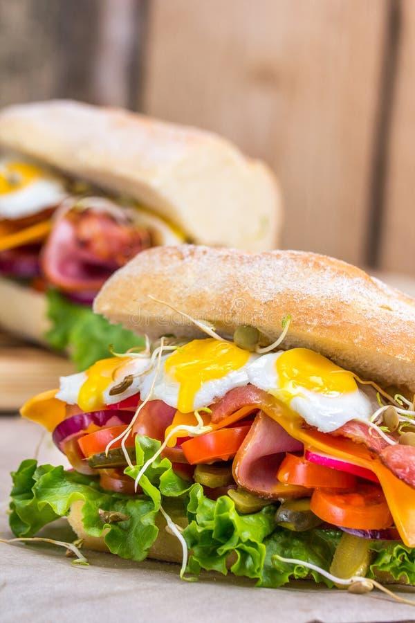 Um sanduíche com bacon, queijo e os ovos de codorniz fritados Um sanduíche com legumes frescos e ervas em um fundo de madeira imagem de stock royalty free