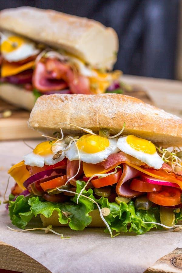 Um sanduíche com bacon, queijo e os ovos de codorniz fritados Um sanduíche com legumes frescos e ervas em um fundo de madeira foto de stock