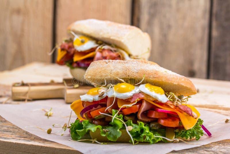 Um sanduíche com bacon, queijo e os ovos de codorniz fritados Um sanduíche com legumes frescos e ervas em um fundo de madeira imagens de stock