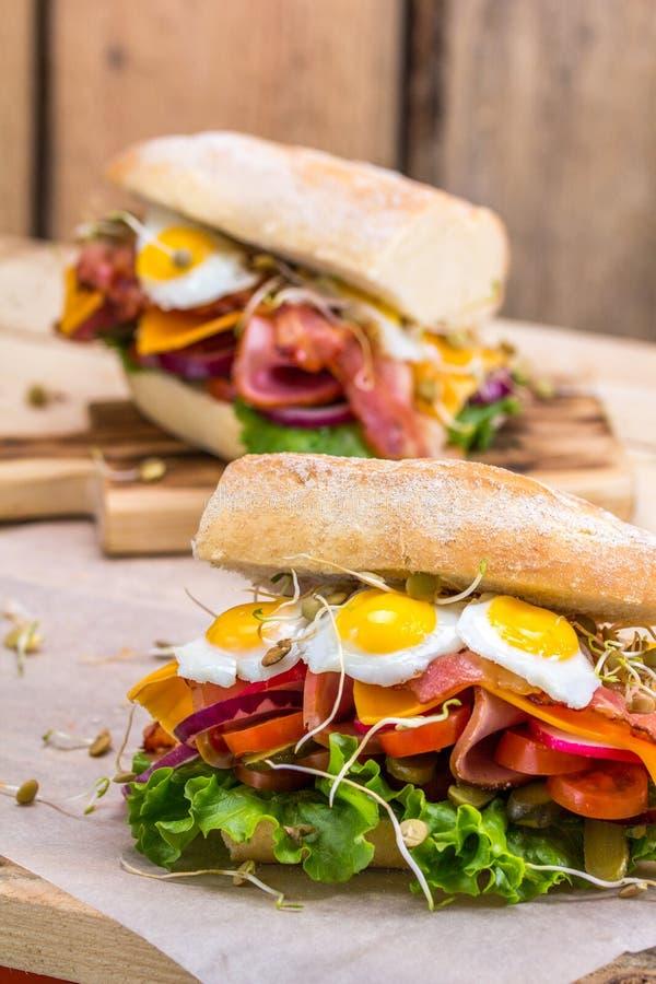 Um sanduíche com bacon, queijo e os ovos de codorniz fritados Um sanduíche com legumes frescos e ervas em um fundo de madeira foto de stock royalty free