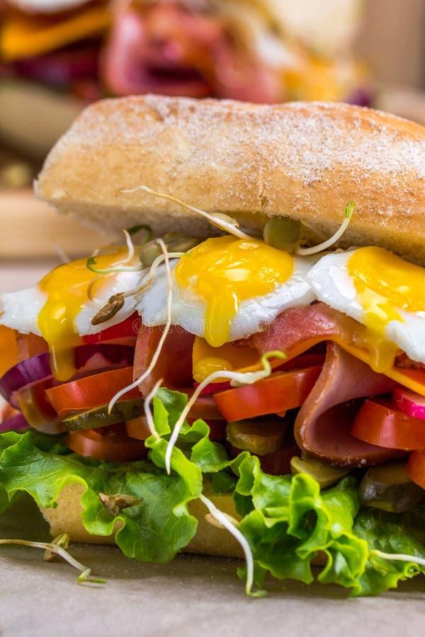 Um sanduíche com bacon, queijo e os ovos de codorniz fritados Um sanduíche com legumes frescos e ervas em um fundo de madeira imagens de stock royalty free