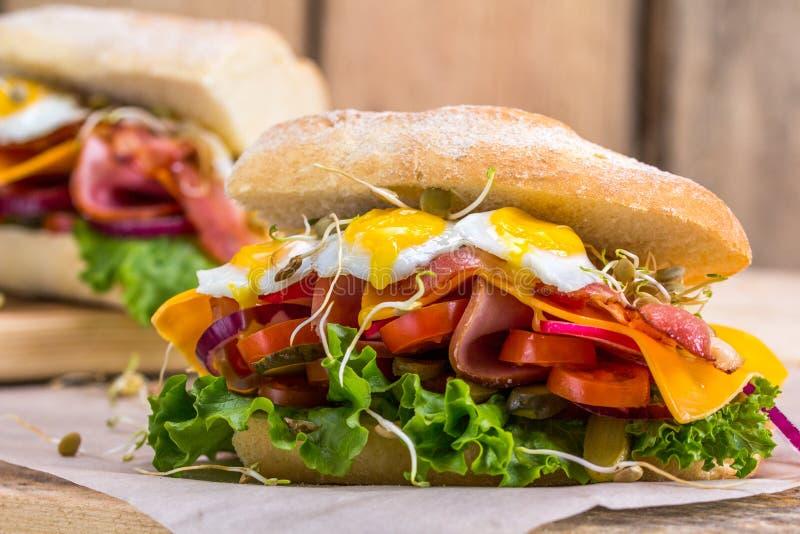 Um sanduíche com bacon, queijo e os ovos de codorniz fritados Um sanduíche com legumes frescos e ervas em um fundo de madeira fotos de stock royalty free