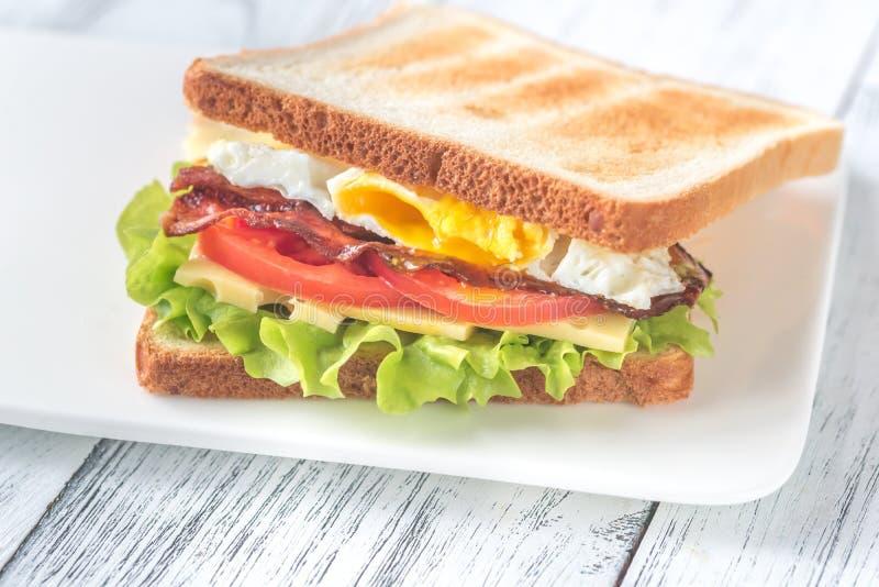 Um sanduíche com ovo frito e bacon imagem de stock royalty free