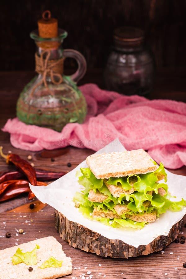 Um sanduíche do pão do cereal, das folhas da alface e das sementes de sésamo fotografia de stock royalty free