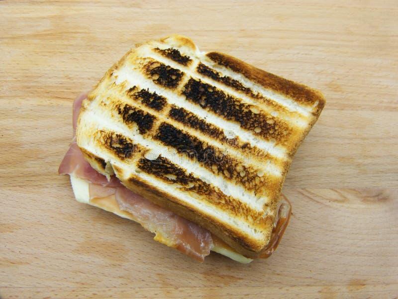 Um sanduíche grelhado do presunto e do queijo no fundo de madeira fotos de stock royalty free