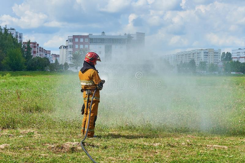 Um sapador-bombeiro do homem de uma mangueira de fogo que molha a grama imagens de stock royalty free