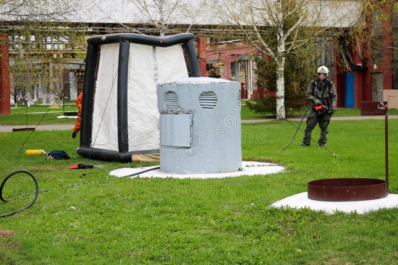 Um sapador-bombeiro profissional em um terno à prova de fogo especial preto prepara-se para montar uma barraca branca do oxigênio fotografia de stock