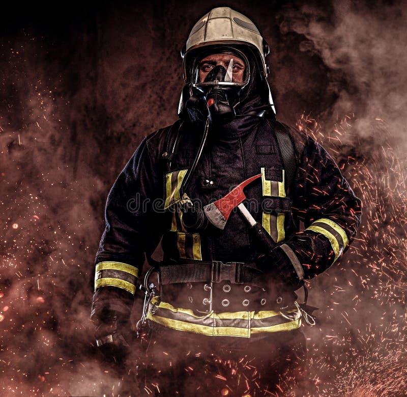 Um sapador-bombeiro vestiu-se em um uniforme em um estúdio foto de stock