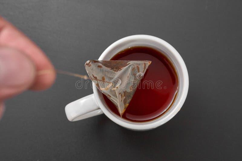 Um saquinho de chá em um copo branco imagens de stock royalty free