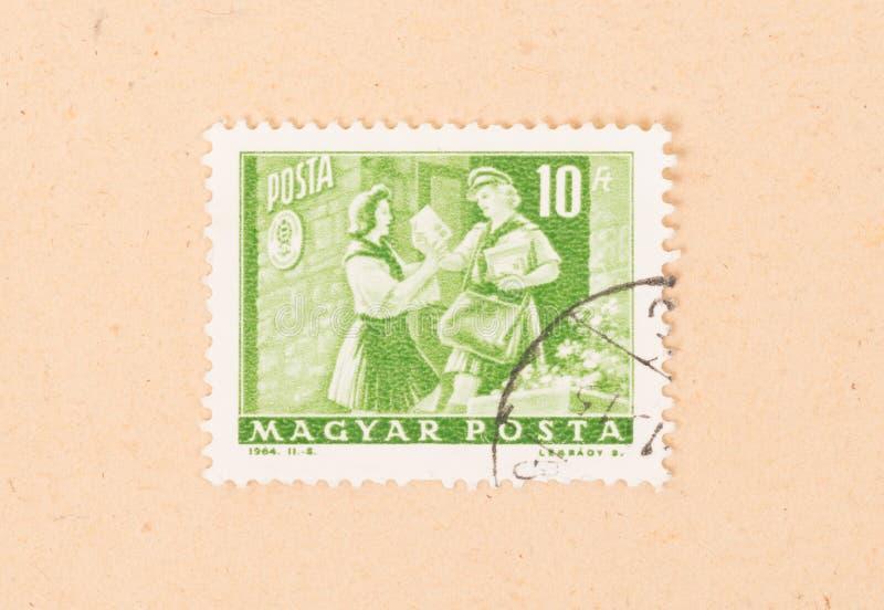 Um selo impresso em Hungria mostra o serviço húngaro do porte postal, cerca de 1964 imagens de stock