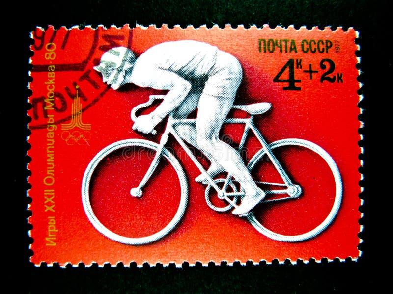 Um selo impresso em Rússia mostra uma imagem de um ciclismo do homem na bicicleta da estrada para os jogos 1980 dos Olympics de v imagens de stock royalty free