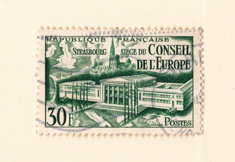 Um selo postal francês do vintage verde velho com uma imagem o conselho ou a construção e o strasbourg de Europa imagem de stock