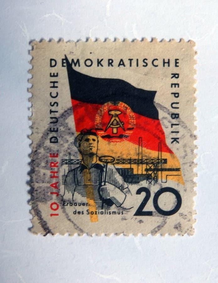 Um selo postal oriental velho com uma imagem de um trabalhador de aço contra a bandeira do gdr foto de stock