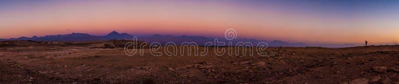 Um silouette que toma uma imagem do por do sol incrível no deserto de Atacama, o Chile fotos de stock