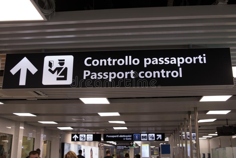 Um sinal bilíngue do aeroporto que indica o sentido do passpor fotos de stock