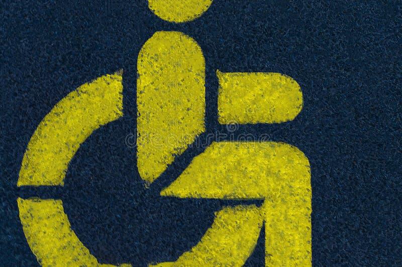 Um sinal da pessoa deficiente pintado com pintura amarela no asfalto em um parque de estacionamento em uma cidade perto de um sho imagem de stock