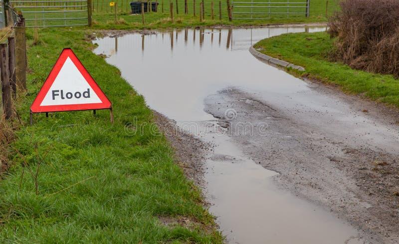 Um sinal de estrada de advertência da inundação ao lado de uma estrada inundada foto de stock