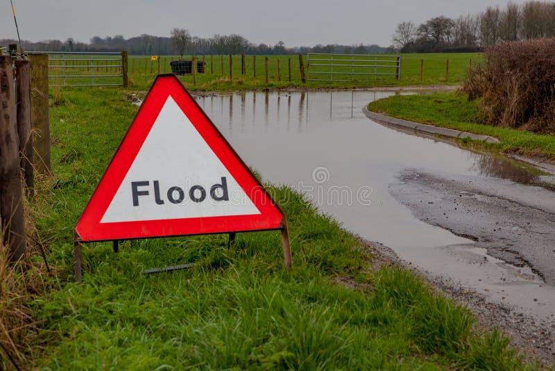 Um sinal de estrada de advertência da inundação ao lado de uma estrada inundada fotografia de stock