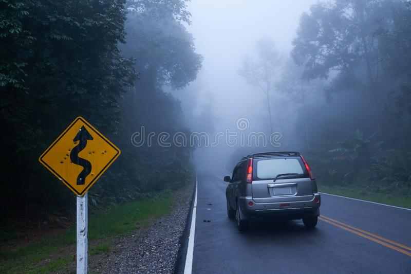 Um sinal de estrada curvy falado enigmaticamente bala e um carro de prata de SUV na estrada asfaltada através de uma floresta tro imagens de stock royalty free