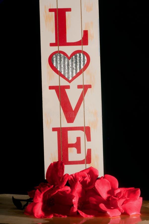 Um sinal de madeira do AMOR é decorado com um ramalhete das rosas foto de stock royalty free
