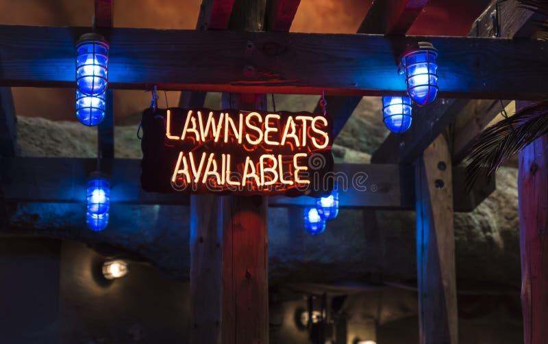 Um sinal de néon iluminado que indica o ` disponível dos lawnseats do ` imagens de stock