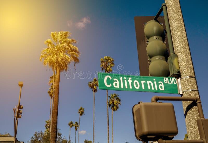 Um sinal de rua de Califórnia em um tráfego Polo com o Sun vermelho que brilha em palmeiras imagem de stock royalty free