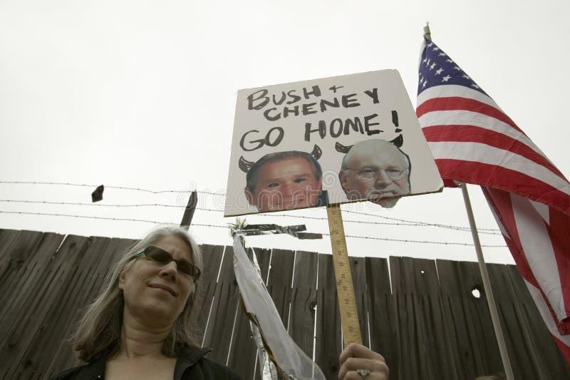 Um sinal mostra a Presidente Bush e o VP Cheney como o diabo com a bandeira dos E.U. em uma marcha de protesto da guerra de anti- ilustração royalty free