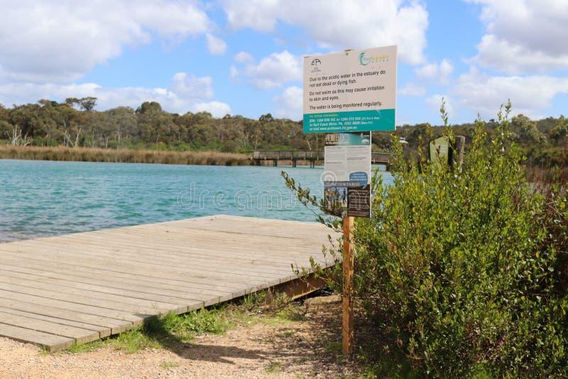 Um sinal que adverte para não nadar ou não comer os peixes inoperantes ou morrendo devido ao ácido fotografia de stock royalty free