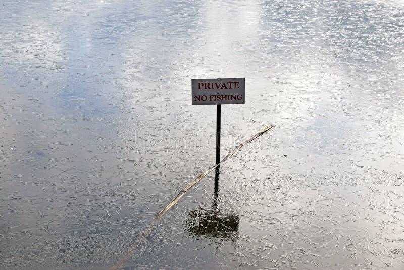 Um sinal que não diz nenhum suporte de pesca no meio de um lago congelado imagens de stock royalty free
