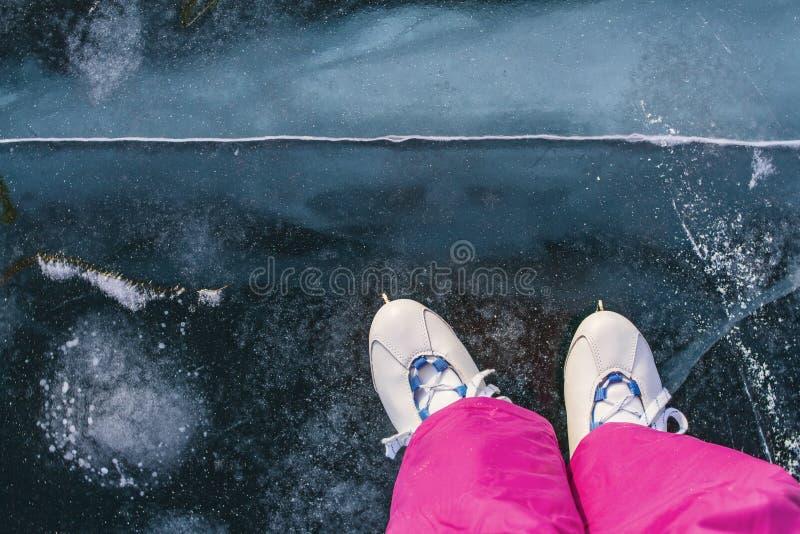 Um skater da menina em patins do vintage e no esqui cor-de-rosa arfa patins no gelo claro azul feericamente bonito do Lago Baikal fotos de stock royalty free