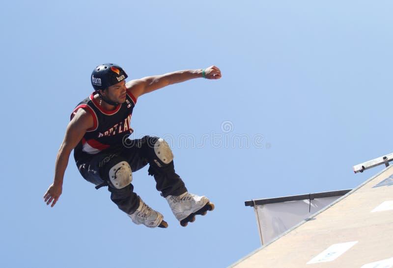 Um skater profissional do rolo executa um truque durante esportes de um extremo fora mostra fotos de stock