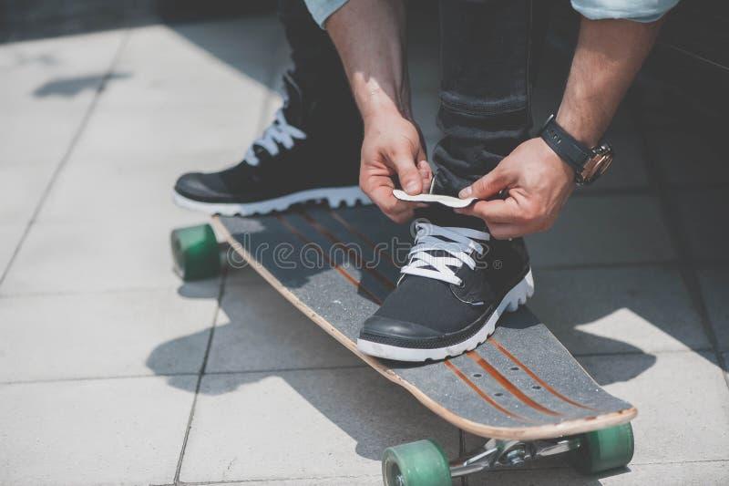 Um skater que amarra laços foto de stock