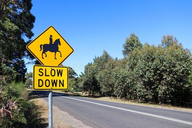 Um Slow Down preto e amarelo, sinal de aviso dos cavaleiros do cavalo perto de um s fotos de stock royalty free