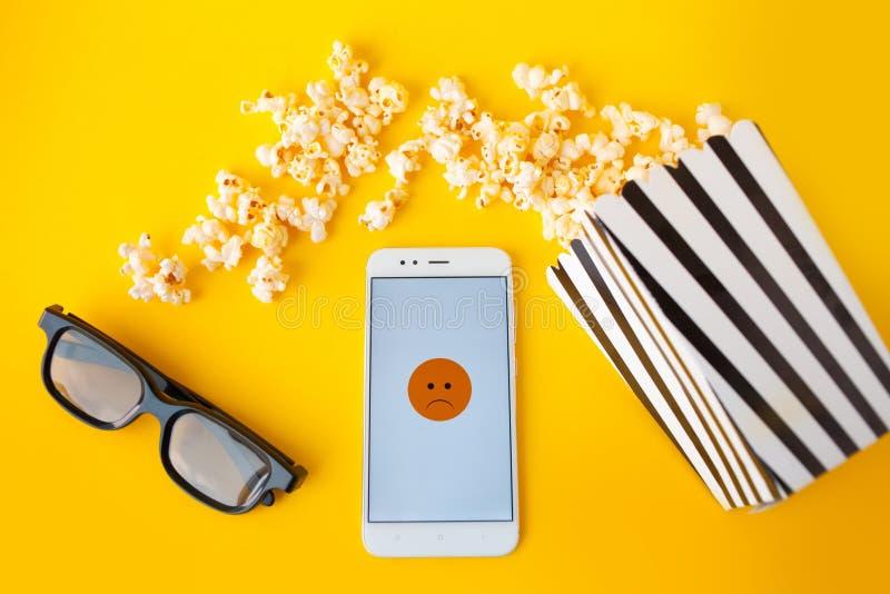 Um smartphone branco com smilies na tela, nos vidros 3d, em uma caixa de papel listrada preto e branco e na pipoca dispersada fotos de stock royalty free
