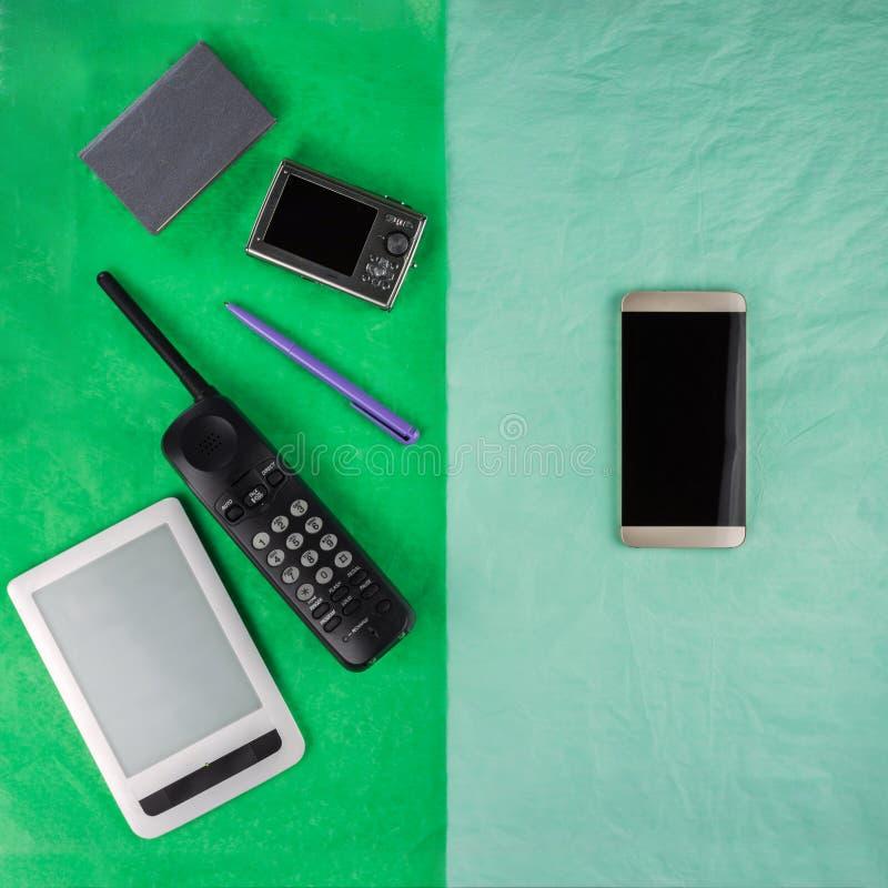 Um smartphone e as coisas que substituem, em metades diferentes de um ret?ngulo dois-colorido fotos de stock