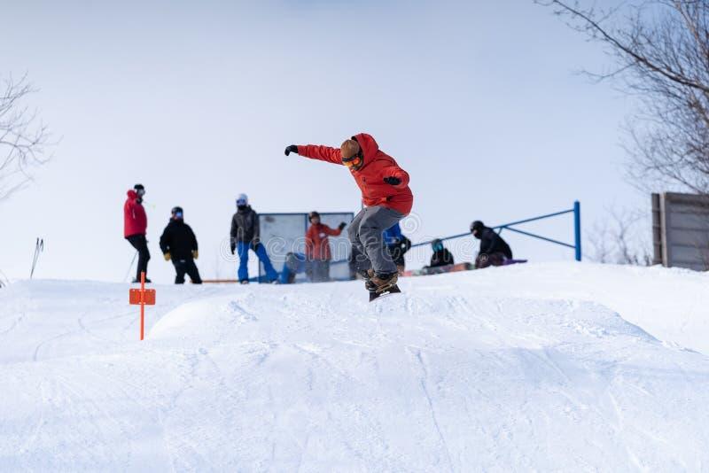 Um snowboarder obtém o ar fora de um salto em um parque do terreno imagens de stock royalty free