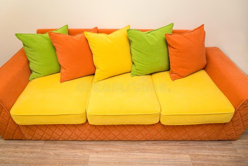 Um sofá amarelo-alaranjado colorido com os descansos verdes, amarelos e alaranjados fotos de stock