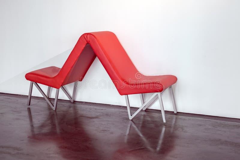 Um sofá de couro vermelho em uma parede branca imagens de stock royalty free