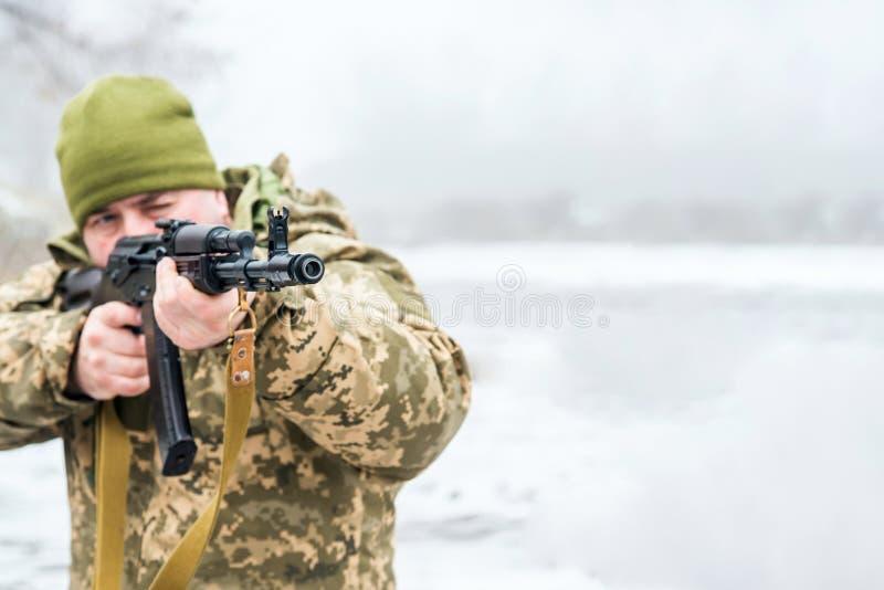 Um soldado com uma arma na camuflagem guarda uma arma em suas mãos e dirige-o para a frente imagens de stock royalty free