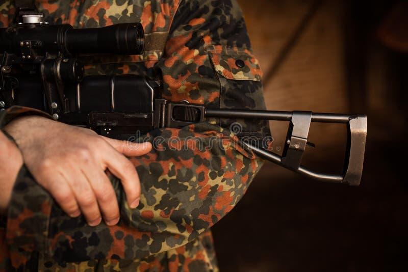 Um soldado está guardando uma arma em suas mãos imagem de stock royalty free