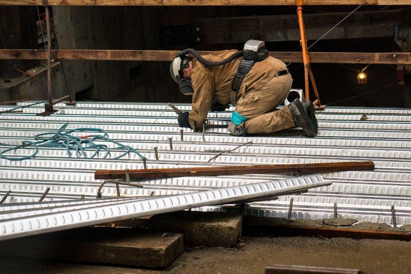 Um soldador especializado do trabalhador da construção que trabalha em um local do trabalho da construção foto de stock royalty free